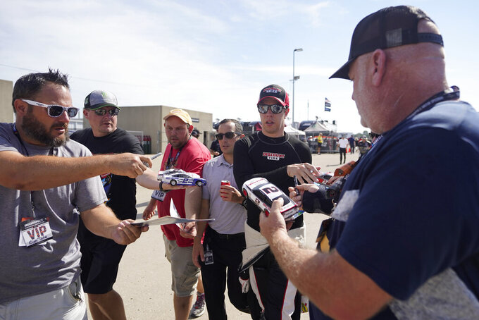Brad Keselowski signs autographs before practice for the NASCAR Cup Series at Indianapolis Motor Speedway, Saturday, Aug. 14, 2021, in Indianapolis. (AP Photo/Darron Cummings)