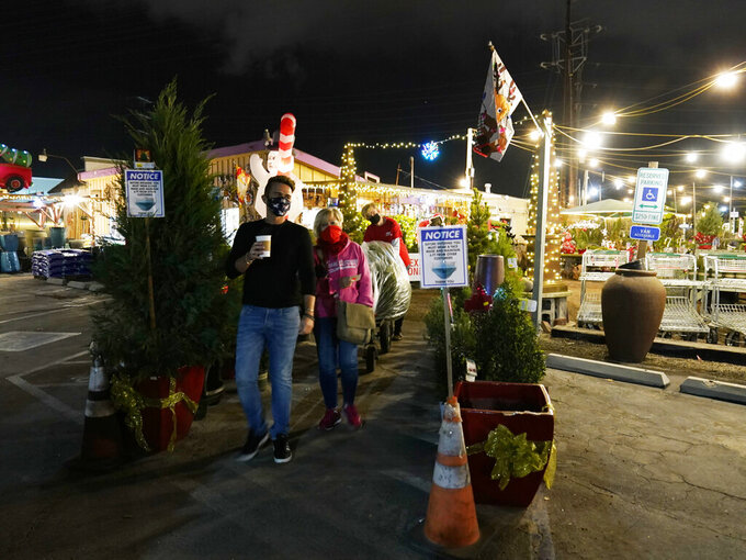 Worker Thomas Temperley, 16, wearing a protective face mask, carries a Christmas tree for Alex Goro and Natalie King at the International Garden and Floral Design Center in El Segundo, Calif., Thursday, Dec. 10, 2020. (AP Photo/Damian Dovarganes)