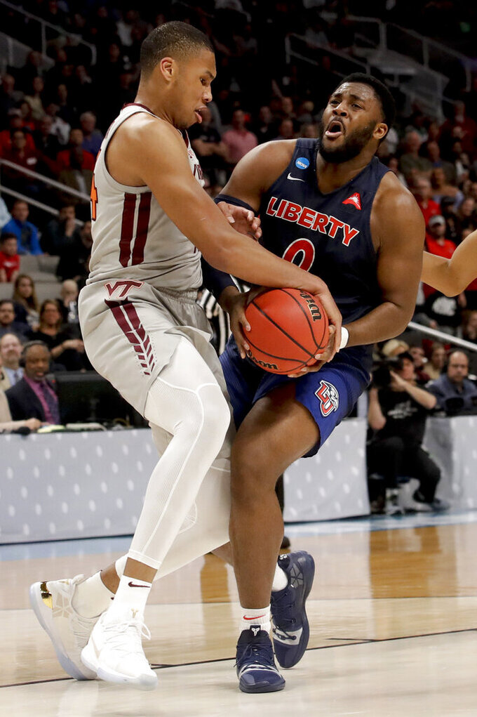 Virginia Tech forward Kerry Blackshear Jr., left, fouls Liberty forward Myo Baxter-Bell during the first half of a second-round game in the NCAA men's college basketball tournament Sunday, March 24, 2019, in San Jose, Calif. (AP Photo/Jeff Chiu)