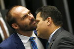 Brazil's Senate President Davi Alcolumbre, right, speaks into the ear of lawmaker Eduardo Bolsonaro, son of the nation's president, during the final voting session on pension reform at the Senate in Brasilia, Brazil, Tuesday, Oct. 22, 2019. The most meaningful impact of the reform is the establishment of a minimum age for retirement at 65 for men and 62 for women. (AP Photo/Eraldo Peres)
