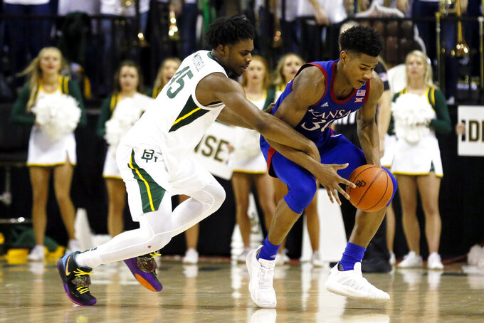 Baylor guard Davion Mitchell, left, defends Kansas guard Ochai Agbaji, right, during the second half of an NCAA college basketball game on Saturday, Feb. 22, 2020, in Waco, Texas. (AP Photo/Ray Carlin)