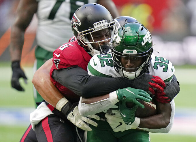 New York Jets running back Michael Carter (32) is tackled by Atlanta Falcons defensive end Dante Fowler Jr. (6) during the first half of an NFL football game between the New York Jets and the Atlanta Falcons at the Tottenham Hotspur stadium in London, England, Sunday, Oct. 10, 2021. (AP Photo/Alastair Grant)