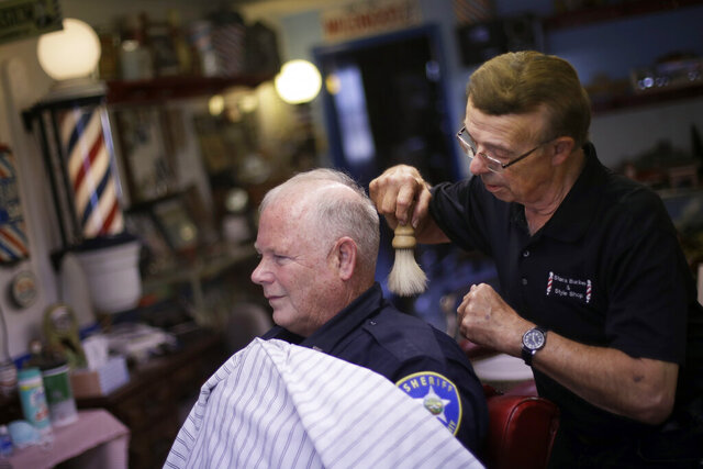 Stan Morin brushes away hair after giving a haircut to Jeff McGee at his barber shop, Thursday, May 21, 2020, in Plainville, Kan. Morin said he has been two to three times busier than normal after reopening a week earlier following a 2-month closure in an effort to stem the spread of the coronavirus. (AP Photo/Charlie Riedel)