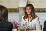 First lady Melania Trump sits down at her table after speaking during the Governors' Spouses' luncheon in the Blue Room of the White House in Washington, Monday, Feb. 10, 2020. (AP Photo/Susan Walsh)