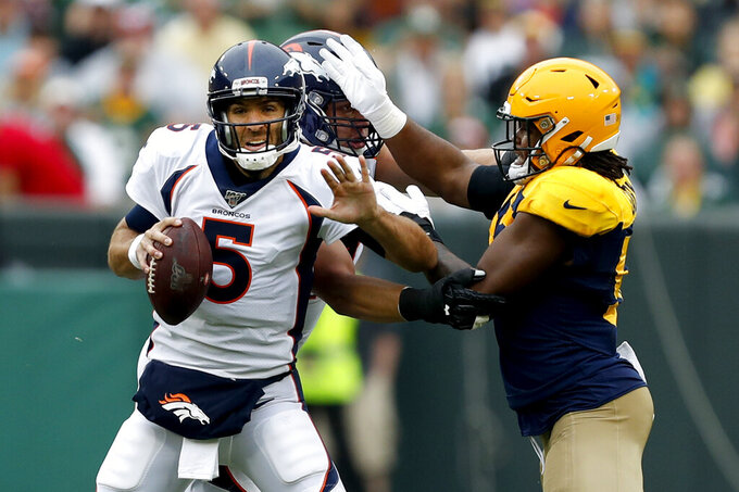 Denver Broncos quarterback Joe Flacco (5) tries to scramble away from Green Bay Packers linebacker Rashan Gary, right, during the first half of an NFL football game Sunday, Sept. 22, 2019, in Green Bay, Wis. (AP Photo/Matt Ludtke)