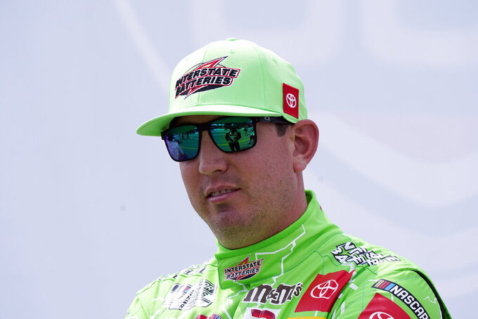 Kyle Busch talks with other drivers before driver introductions at the NASCAR Cup Series auto race at Michigan International Speedway, Sunday, Aug. 22, 2021, in Brooklyn, Mich. (AP Photo/Carlos Osorio)
