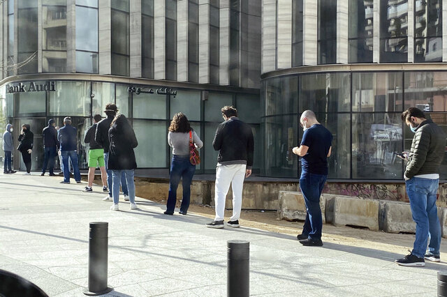 In this March 28, 2020, photo, people stand in a line outside a bank in Beirut, Lebanon, amid a financial crisis and a lockdown imposed by the government to help stem the spread of the coronavirus in Lebanon. (AP Photo/Zeina Karam)