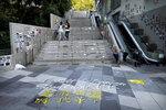 People walk past graffiti reading