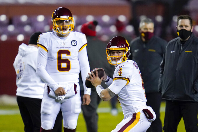 Washington Football Team quarterback Taylor Heinicke (4) warms up for the team's NFL wild-card playoff football game against the Tampa Bay Buccaneers, Saturday, Jan. 9, 2021, in Landover, Md. Watching Heinicke is quarterback Steven Montez (6). (AP Photo/Julio Cortez)