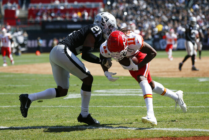 Kansas City Chiefs wide receiver Demarcus Robinson (11) scores a touchdown as Oakland Raiders cornerback Gareon Conley (21) looks on during the first half of an NFL football game Sunday, Sept. 15, 2019, in Oakland, Calif. (AP Photo/D. Ross Cameron)