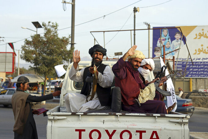 Taliban fighters wave from the back of a pickup truck, in Kabul, Afghanistan, Monday, Aug. 30, 2021. Many Afghans are anxious about the Taliban rule and are figuring out ways to get out of Afghanistan. But it's the financial desperation that seems to hang heavy over the city. (AP Photo/Khwaja Tawfiq Sediqi)