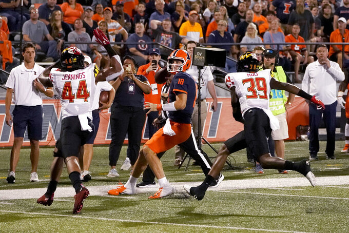 Illinois quarterback Brandon Peters (18) is forced out of bounds by Maryland's Branden Jennings (44) and Deshawn Holt during the first half of an NCAA college football game Friday, Sept. 17, 2021, in Champaign, Ill. (AP Photo/Charles Rex Arbogast)
