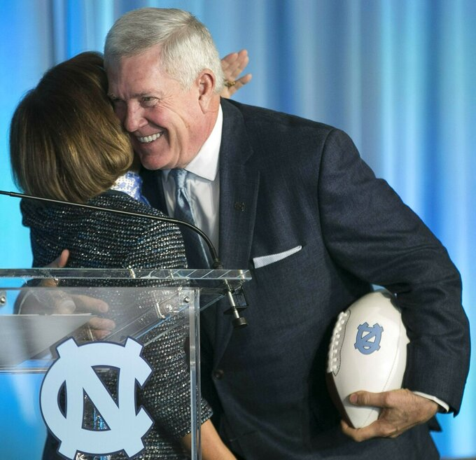 FILE - In this Nov. 27, 2018, file photo, Mack Brown, right, embraces University of North Carolina Chancellor Carol Folt as he is introduced as the school's new NCAA college football coach during a news conference, in Chapel Hill, N.C. Brown is back for his second stint as coach of the Tar Heels and is pushing his players for more focus, execution and urgency in spring drills. (Robert Willett/The News & Observer via AP, File)