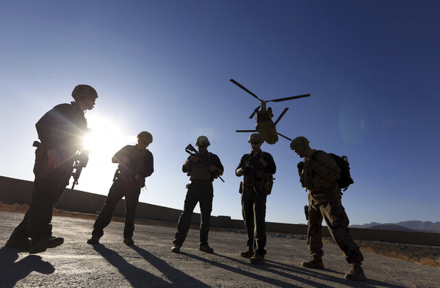 FILE - In this Nov. 30, 2017 file photo, American soldiers wait on the tarmac in Logar province, Afghanistan. The U.S. is pausing movement of troops into Afghanistan and quarantining 1,500 new arrivals to country due to virus. (AP Photo/Rahmat Gul, File)
