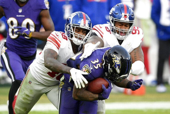 Baltimore Ravens running back Gus Edwards (35) is brought down by New York Giants linebacker Tae Crowder (48) and defensive end B.J. Hill (95) during the second half of an NFL football game, Sunday, Dec. 27, 2020, in Baltimore. The Ravens won 27-13. (AP Photo/Nick Wass)