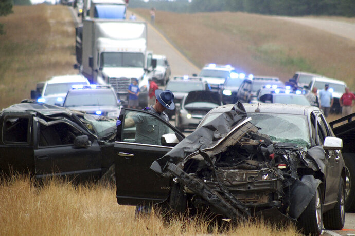 A Mississippi Highway Patrol state trooper investigates a wreck on U.S. Highway 45 south of Scooba in Kemper County, Miss., Wednesday, June 5, 2019. Three people were killed and several were injured Wednesday in a wreck involving multiple vehicles, including a school bus with no children aboard, on a rural Mississippi highway not far from the scene of another crash that killed eight people two days earlier. (Bill Graham/The Meridian Star via AP)