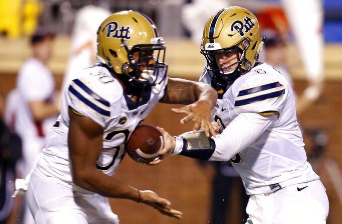 """FILE - In this Nov. 2, 2018, file photo, Pittsburgh quarterback Kenny Pickett (8) hands off to running back Qadree Ollison (30) during the first half of an NCAA college football game against Virginia in Charlottesville, Va. Pickett doesn't take offense to the term """"game manager."""" The sophomore is just fine if all he has to do is hand the ball off and watch the running game go to work, something he hopes to do frequently on Saturday when the Panthers play No. 2 Clemson in the ACC Championship.  (AP Photo/Steve Helber)"""