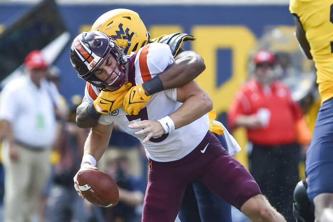 Virginia Tech quarterback Braxton Burmeister (3) is sacked by West Virginia linebacker Jared Bartlett (10) during the second half of  an NCAA college football game in Morgantown, W.Va., Saturday, Sep. 18, 2021. (AP Photo/William Wotring)