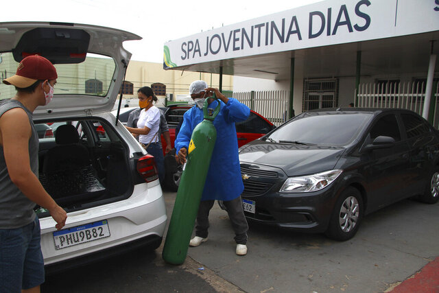 A health worker helps the relatives of patients with COVID-19 load an empty oxygen tank into their car which they will take to a store to be refilled and bring back, outside the Joventina Dias Hospital in Manaus, Brazil, Friday, Jan. 15, 2021. Hospital staff and relatives of COVID-19 patients rushed to provide facilities with oxygen tanks just flown into the city as doctors chose which patients would breathe amid dwindling stocks and an effort to airlift some of them to other states. (AP Photo/Edmar Barros)