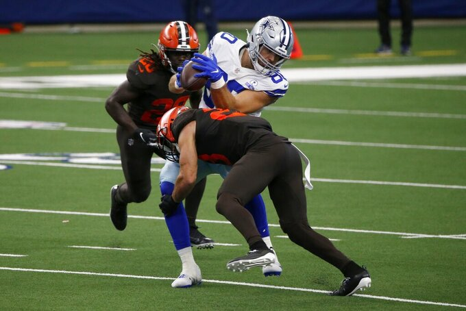 Dallas Cowboys tight end Blake Bell (80) catches a pass as Cleveland Browns cornerback Kevin Johnson (28) and Tavierre Thomas (20), rear, make the stop in the second half of an NFL football game in Arlington, Texas, Sunday, Oct. 4, 2020. (AP Photo/Michael Ainsworth)
