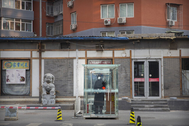 In this Monday, Jan. 27, 2020 photo, a security guard wearing a face mask stands in a glass cubicle on an empty street in Beijing. Fears of a virus outbreak have kept many indoors and at home in China's capital. Cultural landmarks such as the Great Wall and Forbidden City have closed their doors to visitors, nearly deserted shopping malls have reduced their operating hours, and restaurants that remain open draw just a handful of customers. (AP Photo/Mark Schiefelbein)