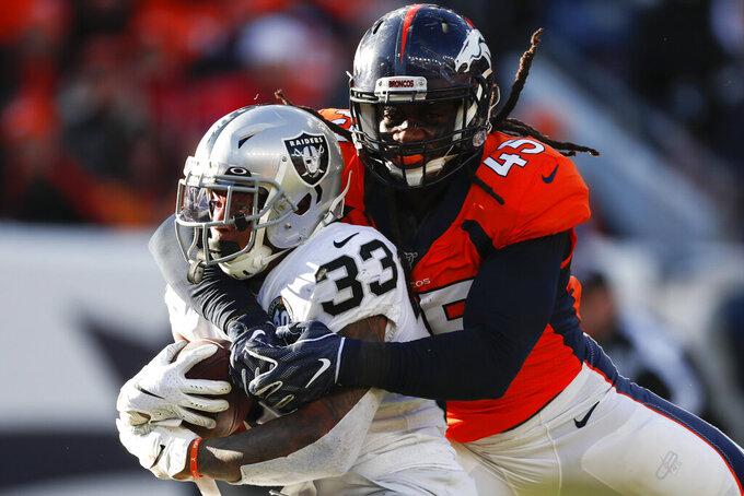 Oakland Raiders running back DeAndre Washington (33) is hauled down by Denver Broncos linebacker A.J. Johnson (45) during the first half of an NFL football game Sunday, Dec. 29, 2019, in Denver. (AP Photo/David Zalubowski)