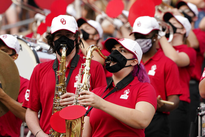 FILE - In this Saturday, Sept. 12, 2020 file photo, a reduced size Oklahoma band performs in the stands in the second half of an NCAA college football game against Missouri State in Norman, Okla.  Marching bands, part of the game since its beginning more than a century ago, are idled or toned down across the country. They won't be able to perform in front of the usual crowds at football games, dramatically changing the experience.    (AP Photo/Sue Ogrocki, File)