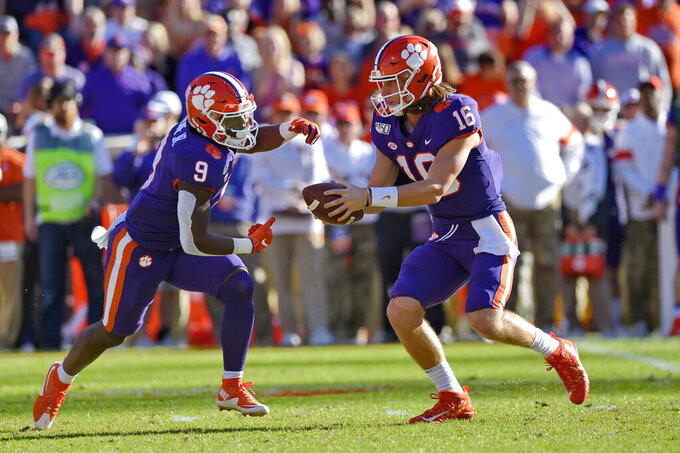 Clemson quarterback Trevor Lawrence (16) hands the ball off to running back Travis Etienne (9) during the first half of an NCAA college football game against Wofford, Saturday, Nov. 2, 2019, in Clemson, S.C. (AP Photo/Richard Shiro)