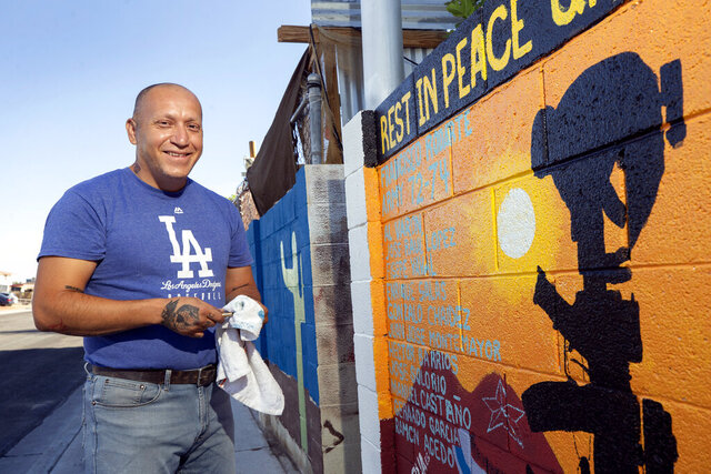 Marine veteran Cesar Lopez poses by a mural on a wall outside his home in Las Vegas, Wednesday, Aug. 12, 2020. Lopez, a legal resident but not a U.S. citizen, was deported to Mexico about eight years ago based on a conviction from 2000. He now works on behalf of other veterans who have been deported. (Steve Marcus/Las Vegas Sun via AP)