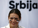 In this photo taken Sept. 25, 2019, a young Serbian rights group activist has her face painted to confuse the Huawei surveillance video cameras with face-recognition software installed in Belgrade, Serbia. With public authorities disclosing little about how the cameras work, the group has set up a tent to ask pedestrians whether they know they are being watched. (AP Photo/Darko Vojinovic)
