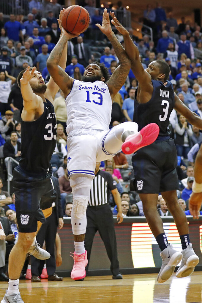 Butler forward Bryce Golden (33) and guard Kamar Baldwin (3) defend against Seton Hall guard Myles Powell (13) during the second half of an NCAA college basketball game Wednesday, Feb. 19, 2020, in Newark, N.J. Seton Hall won 74-72. (AP Photo/Kathy Willens)