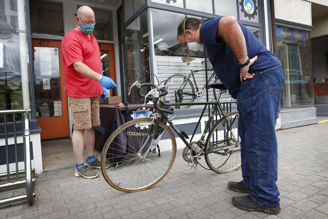 In this Tuesday, June 9, 2020 photo, Harvey Curtis, left, discusses repair plans with customer Jack Matheson outside Sidecountry Sports, a bike shop in Rockland, Maine. Matheson is looking forward to getting his 40-year-old Raleigh back on the road. (AP Photo/Robert F. Bukaty)
