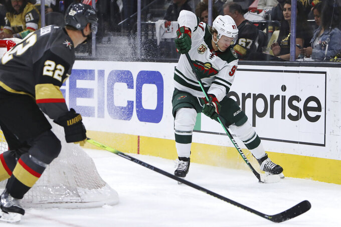 Minnesota Wild left wing Kirill Kaprizov (97) reverses the puck next to Vegas Golden Knights defenseman Nick Holden (22) during the third period of Game 7 of an NHL hockey Stanley Cup first-round playoff series Friday, May 28, 2021, in Las Vegas. (AP Photo/Joe Buglewicz)