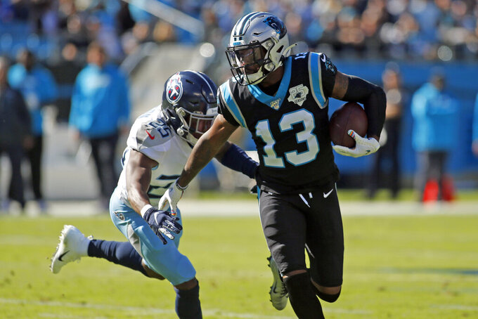 Carolina Panthers wide receiver Jarius Wright (13) runs the ball while Tennessee Titans cornerback Adoree' Jackson (25) looks for the tackle during the first half of an NFL football game in Charlotte, N.C., Sunday, Nov. 3, 2019. (AP Photo/Brian Blanco)
