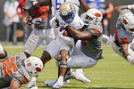 Tulsa running back Shamari Brooks (3) is tackled by Oklahoma State defensive tackle Jayden Jernigan (42) in the second half of an NCAA college football game, Saturday, Sept. 11, 2021, in Stillwater, Okla. (AP Photo/Sue Ogrocki)