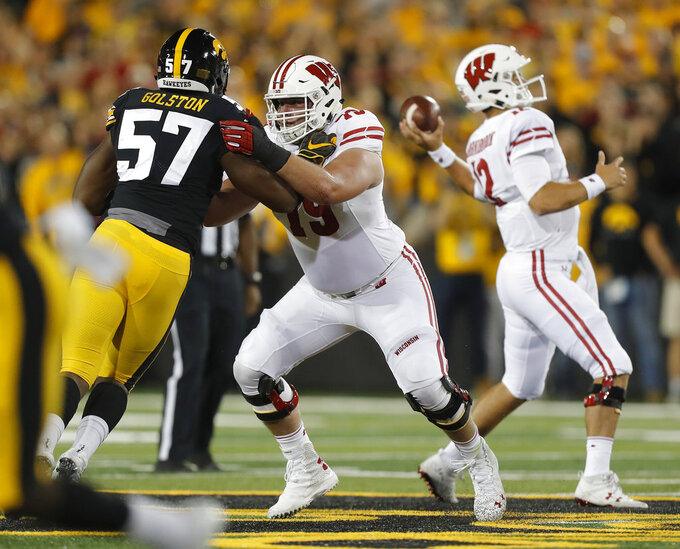 FILE - In this Sept. 22, 2018 file photo Wisconsin offensive lineman David Edwards, center, blocks Iowa defensive end Chauncey Golston, left, from quarterback Alex Hornibrook, right, during the first half of an NCAA college football game in Iowa City. A loss at the Big House left Hornibrook and his teammates reassessing their goals. The playoffs are now out of reach for the 23rd-ranked Badgers after getting blown out at Michigan, though they still control their destiny in the Big Ten West. Win their last six regular season games, starting on Saturday, Oct. 20, 2018 against visiting Illinois, and the Badgers will go back to Indianapolis for the conference title game in December. (AP Photo/Matthew Putney, file)