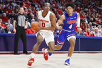 Dayton's Rodney Chatman (0) drives against Houston Baptist's Myles Pierre (4) during the first half of an NCAA college basketball game, Tuesday, Dec. 3, 2019, in Dayton, Ohio. (AP Photo/John Minchillo)