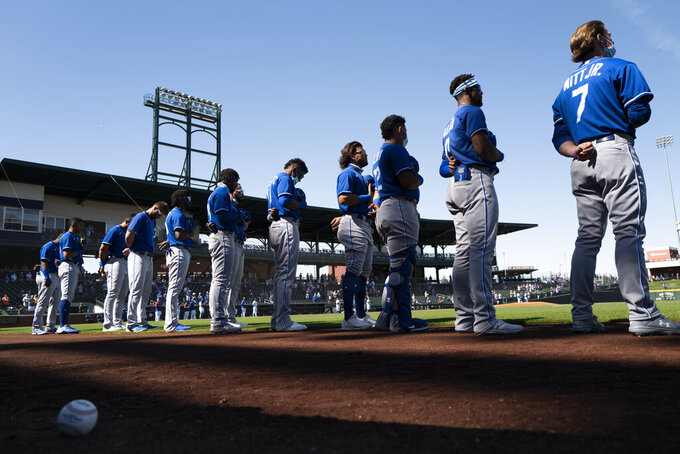 Kansas City Royals players listen to the national anthem before the team's spring baseball game against the Chicago Cubs in Mesa, Ariz., Tuesday, March 2, 2021. (AP Photo/Jae C. Hong)