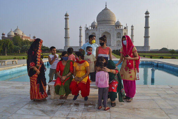 A group gathers for a photo at the Taj Mahal monument that was reopened to public after the lockdown to curb the spread of coronavirus in Agra, India, Wednesday, June 16, 2021. (AP Photo)