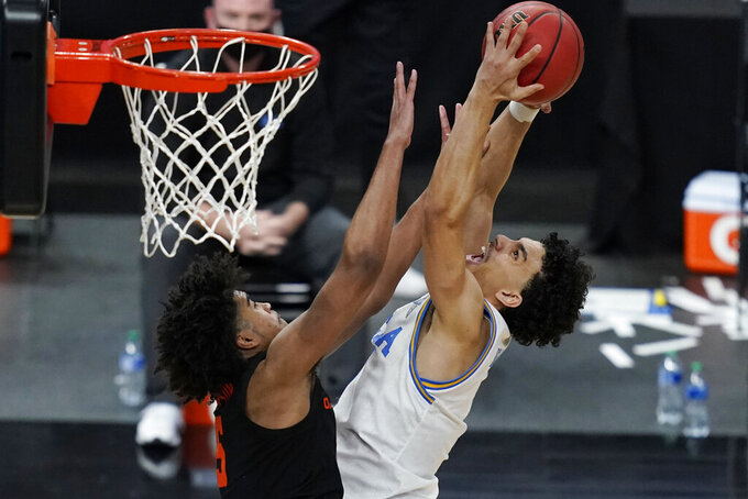 Oregon State's Ethan Thompson, left, fouls UCLA's Jules Bernard during the second half of an NCAA college basketball game in the quarterfinal round of the Pac-12 men's tournament Thursday, March 11, 2021, in Las Vegas. (AP Photo/John Locher)