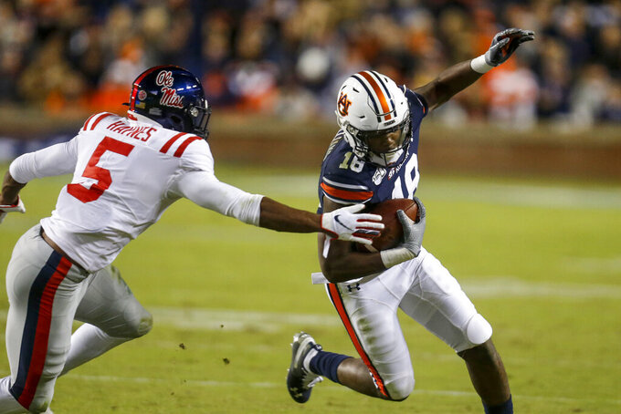 Auburn wide receiver Seth Williams (18) tries to get away from Mississippi defensive back Jon Haynes (5) during the second half of an NCAA college football game Saturday, Nov. 2, 2019, in Auburn, Ala. (AP Photo/Butch Dill)