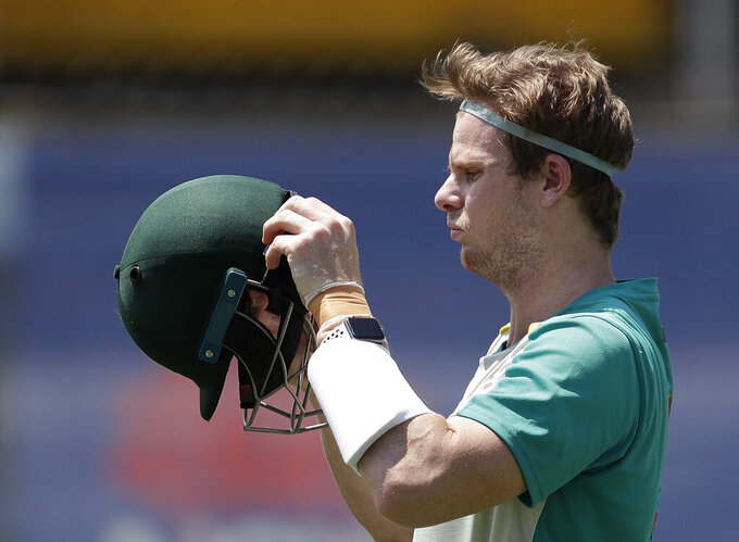 Australia's Steve Smith prepares to put on his helmet before batting in the nets as they train at the Sydney Cricket Ground in Sydney, Tuesday, Jan. 5, 2021, ahead of their cricket test against India starting Thursday. (AP Photo/Rick Rycroft)