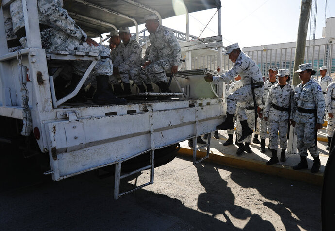 National Guards get on a truck in Ciudad Hidalgo, Mexico, Friday, Jan. 17, 2020 as they deploy along southern border with Guatemala. United States officials are crediting tough measures taken over the past year and cooperation from regional governments for sharply reducing the number of Central American migrants who responded to a call for a new caravan. (AP Photo/Marco Ugarte)