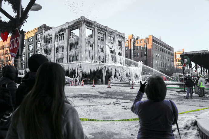 FILE - In this Jan. 10, 2016 file photo, spectators watch efforts to douse a fire in a building in Omaha, Neb., where M's Pub was located. The Nebraska Supreme Court is allowing a lawsuit to continue against an Omaha natural gas utility for a 2016 fire that destroyed part of the downtown Omaha's Old Market. The ruling Friday, Jan. 22, 2021, affirms the finding of a lower court that rejected Metropolitan Utilities District's request for summary judgment to be excused from the lawsuit. (AP Photo/Nati Harnik File)