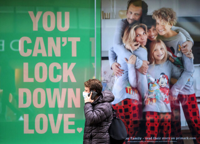 A man walks past a poster in the window of a clothing shop in Manchester, England, Saturday Nov. 28, 2020. A four-week national lockdown to curb the spread of coronavirus is still restricting civil liberties and will put more pressure on shops to attract customers back to shopping streets when restrictions are relaxed in the run-up to Christmas.  (Danny Lawson/PA via AP)