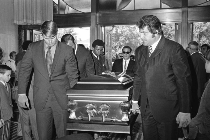 "FILE  - In this June 19, 1970, file photo. Chicago Bears teammates of Brian Piccolo carry his coffin into Christ the King Church for funeral services in Chicago. From left, front to back, are Randy Jackson, Dick Butkus, and Gale Sayer. Ed O'Bradovich is at right. Hall of Famer Gale Sayers, who made his mark as one of the NFL's best all-purpose running backs and was later celebrated for his enduring friendship with a Chicago Bears teammate with cancer, has died. He was 77. Nicknamed ""The Kansas Comet"" and considered among the best open-field runners the game has ever seen, Sayers died Wednesday, Sept. 23, 2020, according to the Pro Football Hall of Fame. (AP Photo/File)"