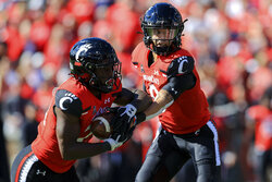 Cincinnati running back Jerome Ford, left, takes the hand off from quarterback Desmond Ridder during the first half of an NCAA college football game against UCF, Saturday, Oct. 16, 2021, in Cincinnati. (AP Photo/Aaron Doster)