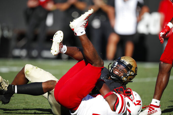 Nebraska cornerback Dicaprio Bootle, bottom, pulls down Colorado wide receiver Laviska Shenault Jr. in overtime of an NCAA college football game Saturday, Sept. 7, 2019, in Boulder, Colo. Colorado won 34-31 in overtime. (AP Photo/David Zalubowski)