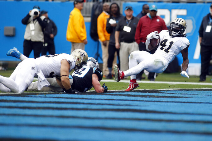 New Orleans Saints running back Alvin Kamara (41) scores a touchdown while Carolina Panthers middle linebacker Luke Kuechly (59) misses the tackle during the first half of an NFL football game in Charlotte, N.C., Sunday, Dec. 29, 2019. (AP Photo/Brian Blanco)
