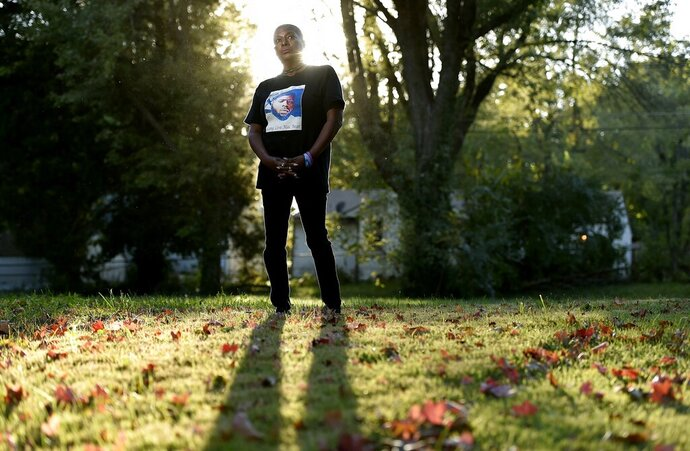 Rhonda Herring poses for a photo wearing a shirt with a picture of her slain son Brandon Herring,  in Raytown, Mo., on Thursday, Oct. 15, 2020. Herring's son was killed in Kansas City in 2017, and found in a creek bed. Herring says she knows who killed him and has experienced threatening behavior by them, including men shooting by her home. She is very dissatisfied with the way police have handled the case. (Jill Toyoshiba/The Kansas City Star via AP)